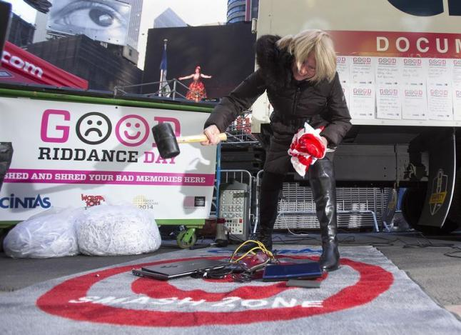 """Jody Watkins smashes old computers as part of """"Good Riddance Day"""" in Times Square in New York"""
